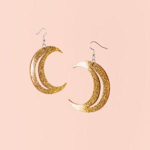 Kuu korvakorut kultaisella glitterillä.