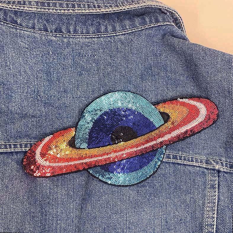 Saturnus silitettävä kangasmerkki farkkutakissa.